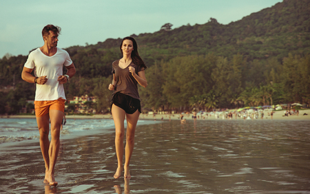 Young, athletic couple jogging on the hot, tropical beach Stock Photo
