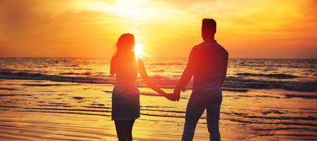 Young, relaxed couple looking at the romantic, tropical sunset Stok Fotoğraf