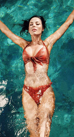 Sensual, young woman realxing in a hot, tropical pool