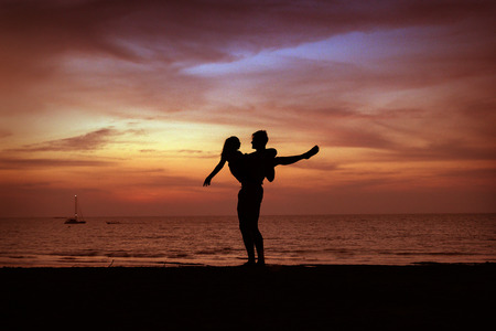 Portrait of a young couple relaxing on a tropical beach - sunset circumstances