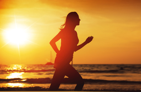 Young athletic woman running on a tropical beach