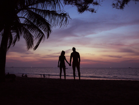Young, relaxed couple looking at the calm, tropical ocean Stock Photo