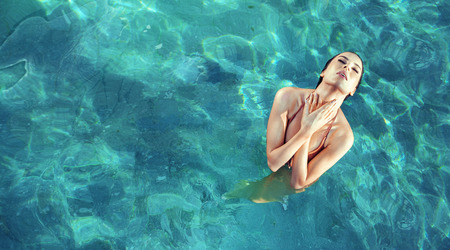 Young, sensual woman realxing in a hot, clear and tropical water Stock Photo