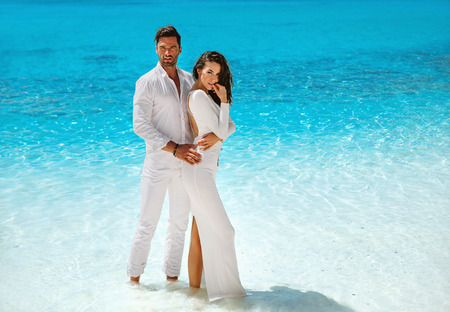 Sensual, elegant couple posing on the tropical, beach