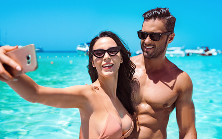 Cheerful couple taking a selfie in a tropical, clear water Stock Photo