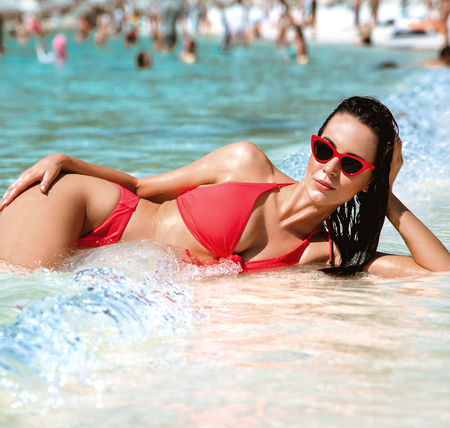 Sensual brunette woman resting on a tropical beach