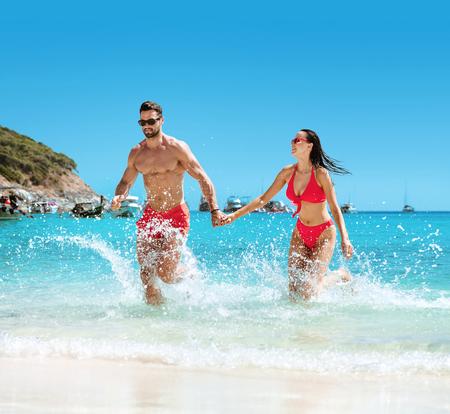 Jong, aantrekkelijk paar dat op een heet, tropisch strand rust Stockfoto