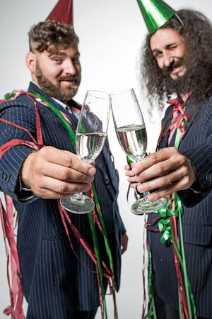 Relaxed party guys holding glasses of champagne