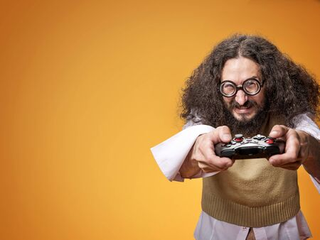 Grappig portret van een slanke nerd die een videogame speelt Stockfoto