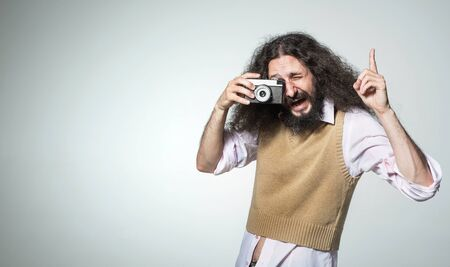 Portrait of a skinny man taking a photo with a vintage camera Stok Fotoğraf
