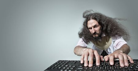 Funny portrait of a freaky nerd working with a computer Imagens