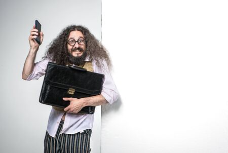 Portrait of a nerdy man holding a briefcase and a cell phone
