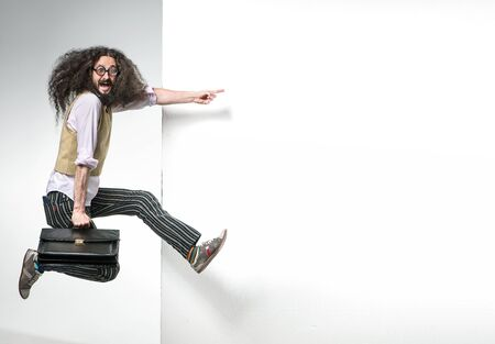 Portrait of a nerd jumping next to the white, commercial board Imagens