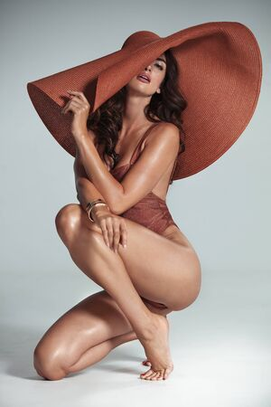 Brunette, sensual model wearing a modern, fashionable hat - isolated
