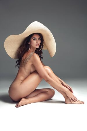 Sensual, nude woman posing with a modern hat Imagens - 133947380