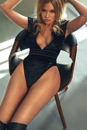 Sensual blonde sitting on a stylish armchair