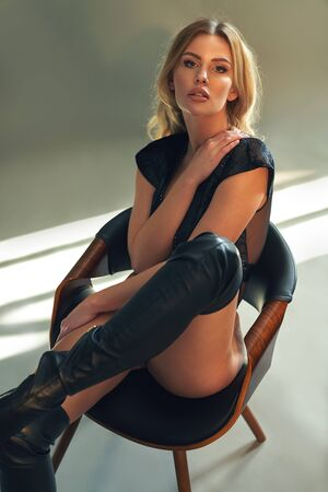 Portrait of a sensual blonde wearing sexy leather boots Imagens - 134477036