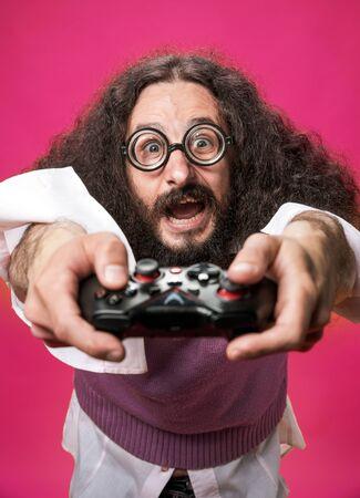Portrait of a funny, bizarre nerd holding a gamepad