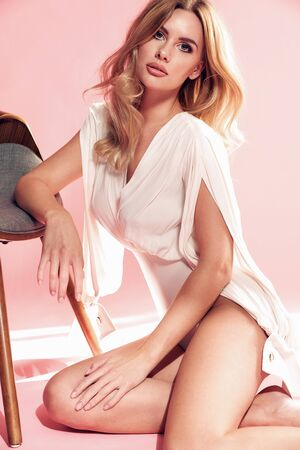 Portrait of a stylish blond lady posing in a pink room Imagens - 133947398