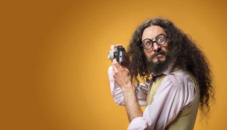 Porträt eines lustigen Nerds, der ein Foto mit einer neuen Digitalkamera macht
