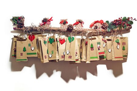 Advent calendar bags hanging on the long, decorated branch
