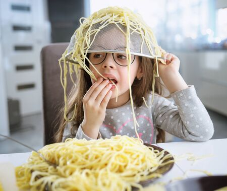 Portrait of a little, cute girl eating a spaghetti pasta Imagens - 143385144