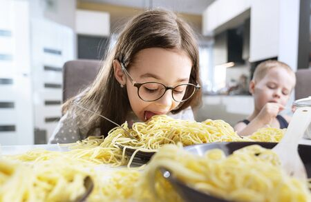 Portrait of a little, cute girl eating a spaghetti pasta Imagens - 143385157