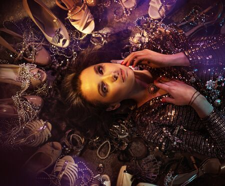 Portrait of a young, attractive woman laying among lots of shoes Imagens - 143385159