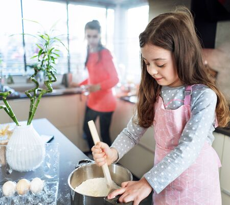 Portrait of a cute little girl making a dough in the home kitchen Imagens - 143385161