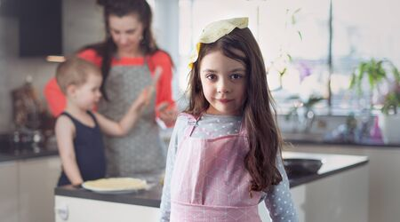 Cheerful family making delicious crepes in the home kitchen Imagens