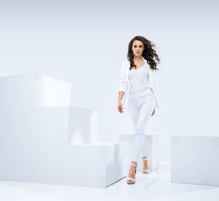 Attractive, young businesswoman walking in the pure white studio