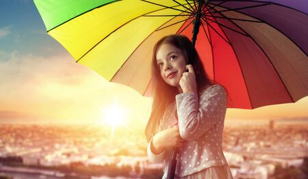Portrait of a cheerful little girl relaxing under the colorful umbrella Imagens