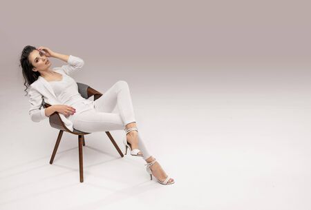 Pretty, young businesswoman relaxing in a stylish armchair