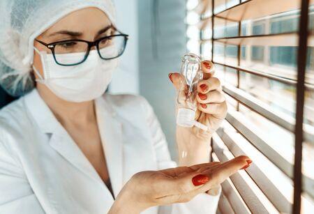 Portrait of a nurse using an antibacterial gel Imagens