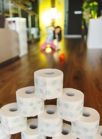 Little girl playing toilet roll bowling in home