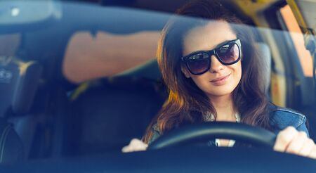 Cheerful, brunette woman riding a car in a sunny day Imagens - 145127325