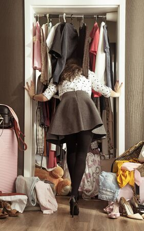 Conceptual picture of an elegant woman looking in the wardrobe