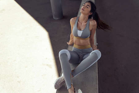 Calm, athletic woman relaxing after running training