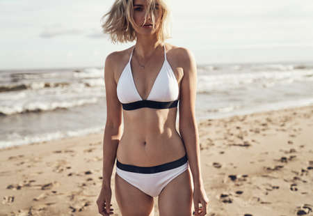 Closeup portrait of an alluring blond lady sauntering on the beach Imagens