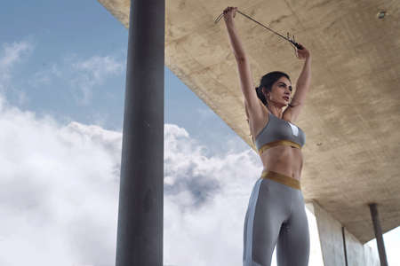 Athletic, brunette woman doing the jump rope training Imagens