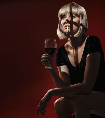 Portrait of an exhausted, pretty blonde drinking wine and smoking