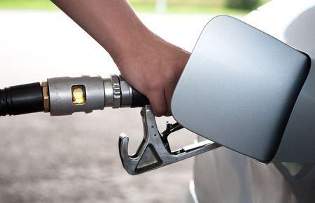 gasolinera: Mano rellenado el coche con una bomba de gas