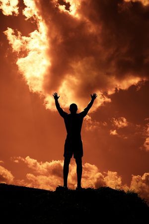 Silhouette of man with arms outstretched to the sky photo