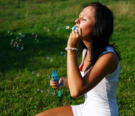 Girl making soap bubbles photo