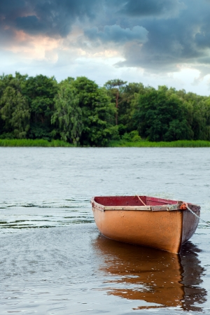 green boat: Lone fishing boat floating on the lake