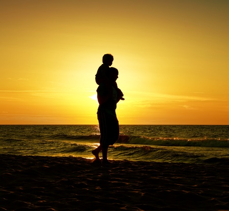 father teaching daughter: father and son at sea on sunset