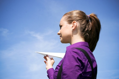 Young businesswoman with paper plane in the hand photo