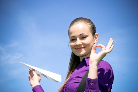 Young caucasian girl with paper plane in the hand photo