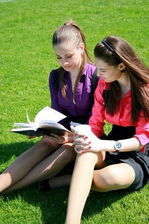 amigas conversando: Dos estudiantes de relajaci�n en la hierba