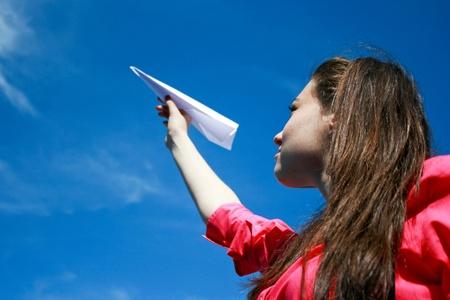 Jonge Kaukasische meisje met papieren vliegtuig in de hand